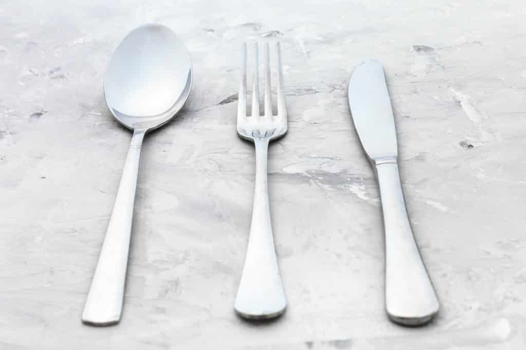 serving set from knife, fork, spoon on concrete