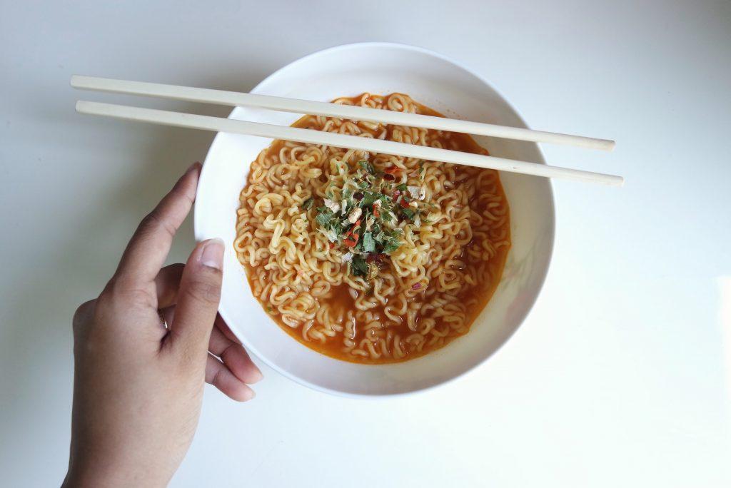 Hand holding a bowl of ramen