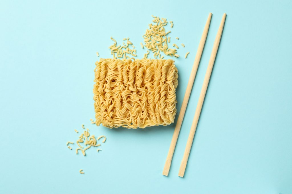 Instant noodles and chopsticks on blue background